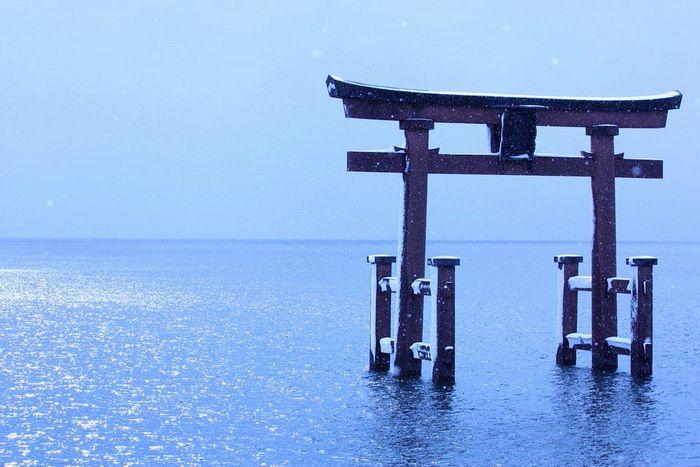 雪の中たたずむ白鬚神社鳥居